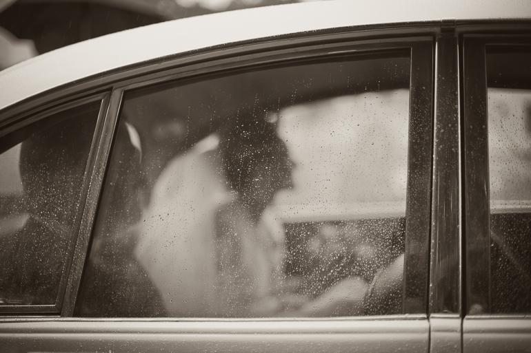 Der Hochzeitsfotograf steht im Regen