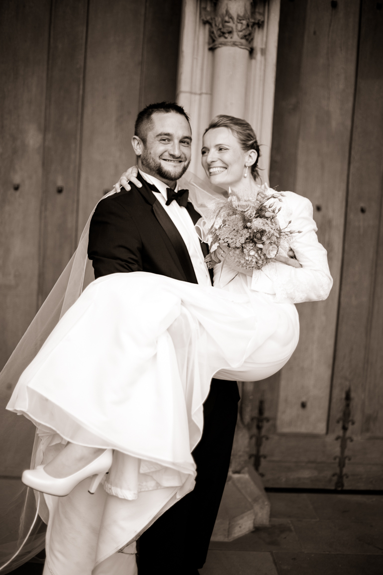 Der Bräutigam trägt die Braut vor der Kirche